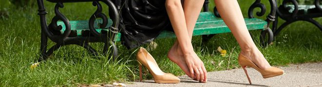Picture: A woman sitting on a park bench takes of one shoe to soothe the corns on her toes. 