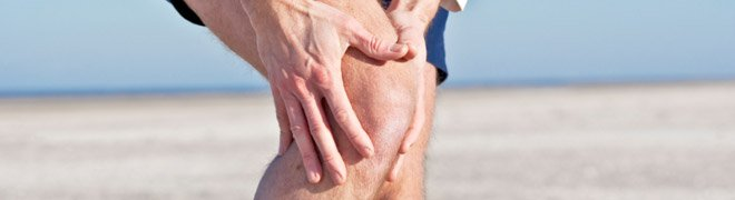 A runner holding his knee as a result of his torn meniscus. 
