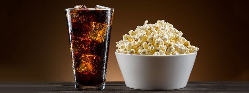 A glass of soda and a bowl of popcorn.