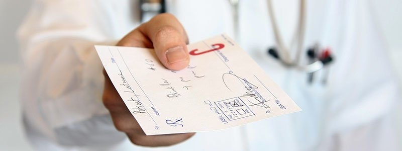 Woman doctor writing on a medical prescription pad.