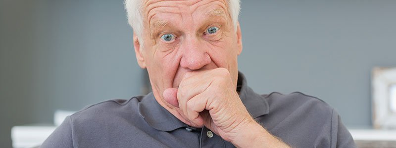 Older man coughing into a napkin.
