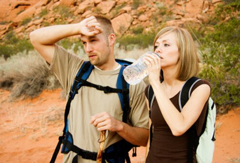 Two hikers are well prepared with water and other supplies during a hike.