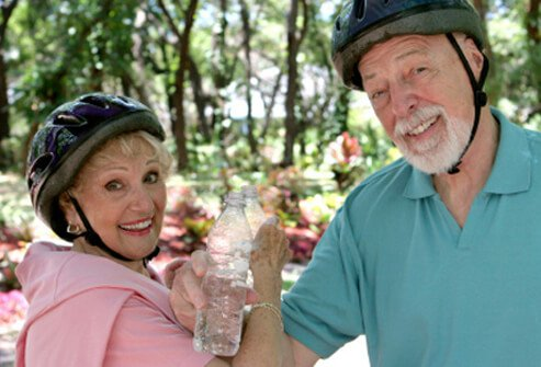 Two seniors drink bottled water while on a bike ride.