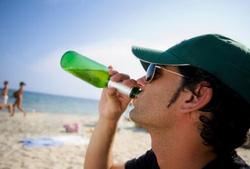 A man drinking beer on a hot day at the beach.