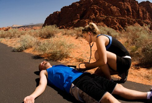 A female runner examines a male runner who has collapsed from heat exhaustion in the desert.