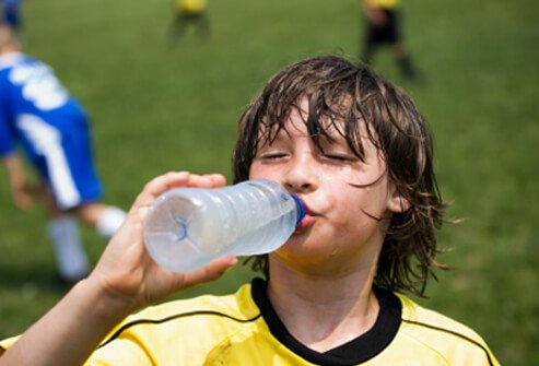 A boy sweating from playing soccer quenches his thirst with water.