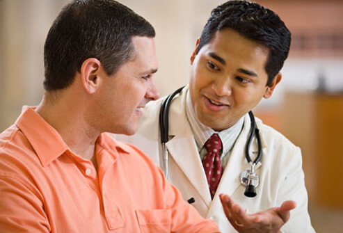 A doctor talking to a man about screening tests.