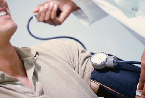 A doctor checking a man's blood pressure.