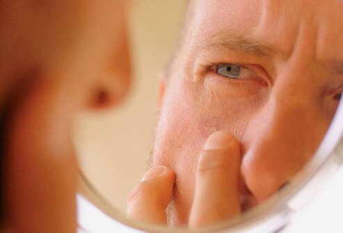 A man checking his skin for signs of cancer.