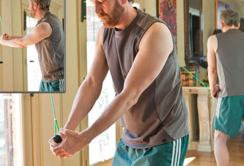 Photo of a man performing the wood chop exercise.