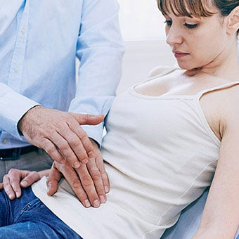 A doctor examining a woman's abdomen to understand her pain.