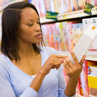 A woman reads a food label at the supermarket.