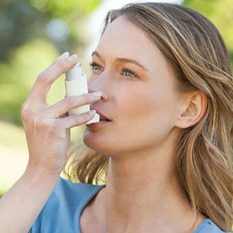 A woman with asthma uses her inhaler.