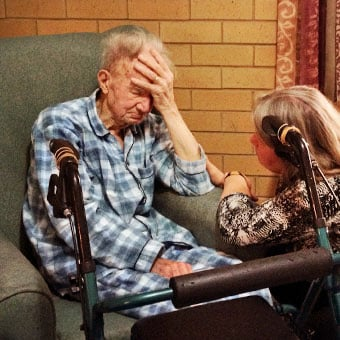 An elderly man in his pajamas with a caregiver.
