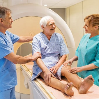 An elderly male patient prepares for an MRI scan.