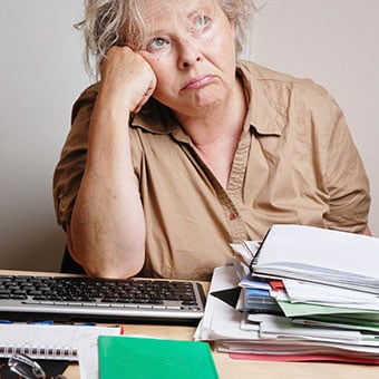 A frustrated woman sitting at a cluttered desk.