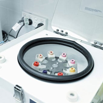 A centrifuge holding various tubes of blood.