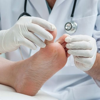 A doctor examines a patient for athlete's foot.