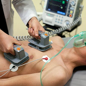 A doctor performs electrical cardioversion on a patient.
