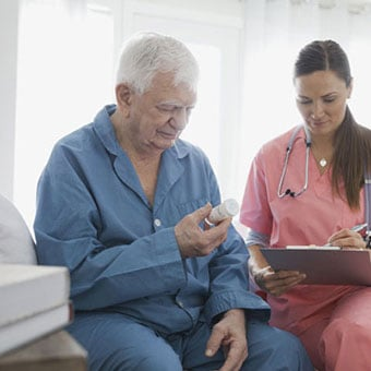 A nurse with an older man holding medication.