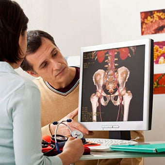 A doctor examines a man experiencing muscle spasms.