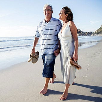 A senior couple walking on the beach.