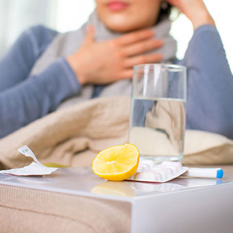 A woman with bronchitis treating herself at home with fluids, lemon and over-the-counter (OTC) medication.
