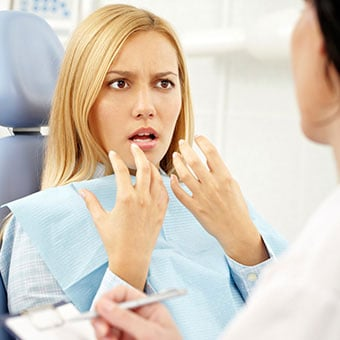 A woman describes canker sore pain to the dentist.