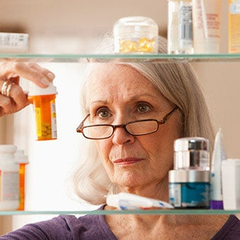 A woman looks at prescription medications in her medicine cabinet.