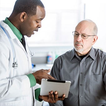 A doctor discussing constipation treatments with a male patient.