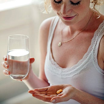 A woman holding medication and a glass of water.