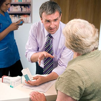 A pharmacist explains medication side effects to a patient.