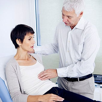 A doctor examines a female patient's abdmominal area due to constipation.