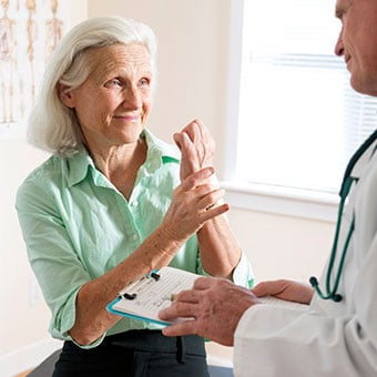 A woman discusses her arthritis wrist pain with her doctor.