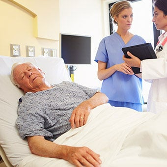 A doctor and nurse discussing complications of a senior patient in the hospital.
