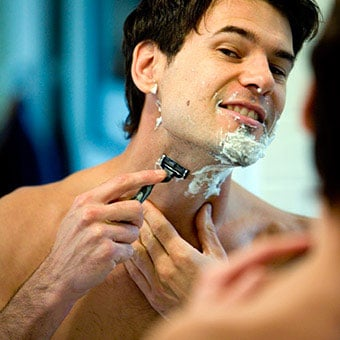 A man shaves his face and neck.