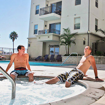 Two young men enjoy an outdoor hot tub.
