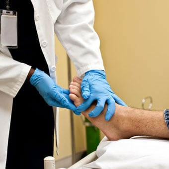 A doctor examines the foot injury of a patient.