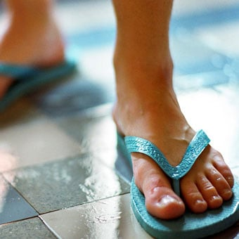 A person wears sandals in in a gym locker room shower.