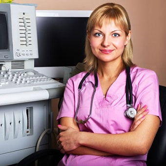 A female doctor sits next to an ultrasound machine.