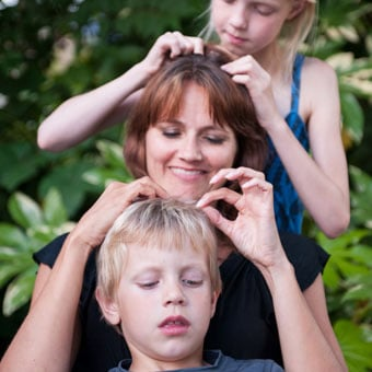 A family checks each other's hair for lice.