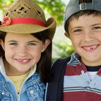 A young girl and boy wear hats.