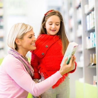 A mother with her daughter shop at the pharmacy for over-the-counter (OTC) head lice medication.