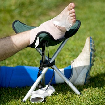 A soccer player rests and elevates his injured foot with a compression bandage and an ice pack.