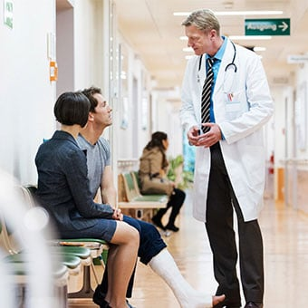 A male patient with a broken leg discusses complications of a hematoma with his doctor.