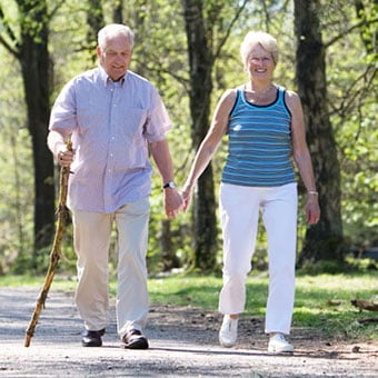 An elderly couple walks through the park.