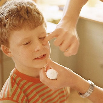A father puts ointment on a boy's face.