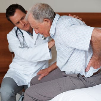 A doctor helping a senior patient in pain.