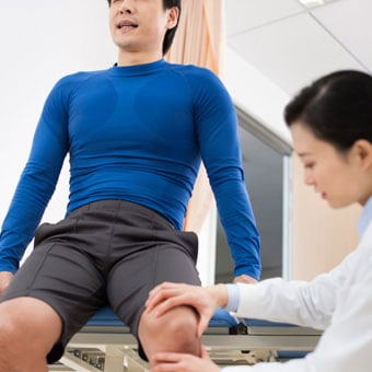 A doctor examines a male patient with knee pain.