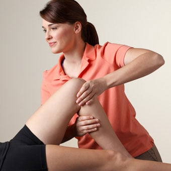 Physical therapist manipulates the knee of a female patient.